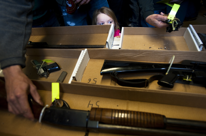 Karson Williams, 3, of Mamont watches hundreds of men, including her father Joe Williams and grandfather Bob Knabb, inspect 97 confiscated guns before bidding during a public auction at Westmoreland County Public Works in Greensburg on Saturday, Nov. 8, 2014. The guns had been in the coroner's office evidence locker for as long as 30 years. Some of the weapons are high-quality, some collectible and many were used in suicides, Coroner Ken Bacha said. State law requires the coroner's office to sell off unclaimed property, including guns, at public auction. This sale is the first the county has had since Bacha's father, Leo, was coroner in the 1980s.
