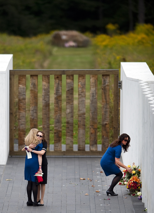 United airlines flight attendants Christina Nixon hugs Anna Stover as Michelle Lea leans over to place flowers, all based in Washington, D.C., during the 13th anniversary service at the Flight 93 National Memorial on Thursday, Sept. 11, 2014, the crash site of United Flight 93, where 40 passengers and crew lost their lives fighting back against terrorists believing to be targeting the U.S. Capitol.
