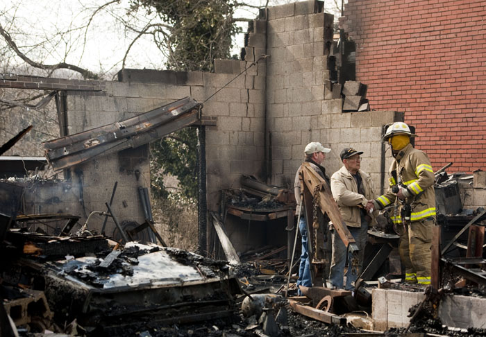 Homeowner Bill Pedder, center, shakes hands with Larimer firefighter Bill Hardy after a garage fire that spread to multiple homes on Monday, March 24, 2014 near the intersection of Cavittsville Road and Western Avenue in North Huntingdon township.