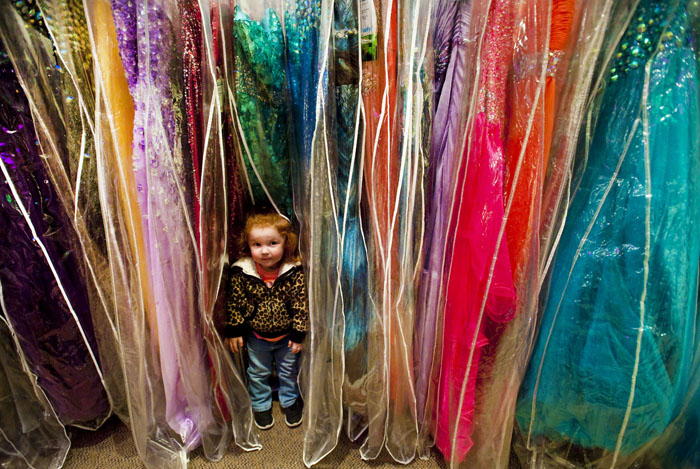 Khloe Lloyd, 2, of Kittanning hides while helping her sister Meagan, a senior at Armstrong High School, find a prom dress on Saturday, April 5, 2014 at MB Bride in Greensburg.