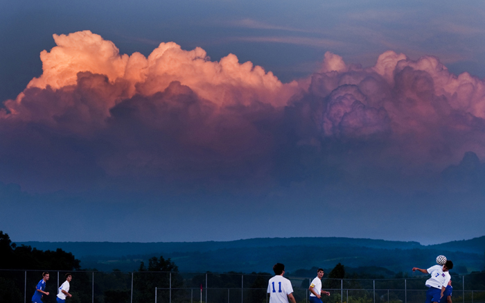 The setting sun illuminates a distant thunderstorm as Mount Pleasant's Brandon Leeder heads the ball against Derry on Thursday, Sept. 4, 2014 at Mount Pleasant High School. Derry won 2-1 in overtime.