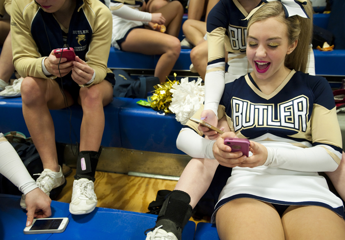 Butler cheerleader Jensen Wehrli plays on her phone with her teammates before competing in the WPIAL Competitive Spirit championships on Saturday, Jan. 10, 2015 at Hempfield Area High School.