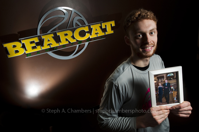 "Junior marketing major and St. Vincent basketball guard Pat Jones, 20, from Frostburg, Md., poses for a portrait while holding a photograph of himself and his late mother Jennie Jones on Thursday, Feb. 19, 2015. Jennie Jones was a breast-cancer patient who attended the team's ""Pink Out"" game for breast-cancer awareness last February. Just before the start of this season in November, Jones died. The team is dedicating this Saturday's ""Pink Out"" to her, with proceeds benefiting the St. Michael's Early Childhood Center in Frostburg, renamed for Jennie Jones after her death. The team then plans to present the center with the donation in November before their tip-off tournament in Frostburg."