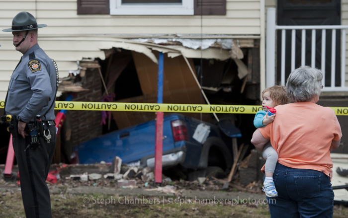 Lacey Weinhofer held by Sue Weinhofer looks toward Trooper Ryan Marmol as he surveys damage caused to a house by a Ford truck on Wednesday, April 8, 2015 in Hutchinson, Sewickley Township. The driver of the truck was flown to Forbes Regional Hospital.