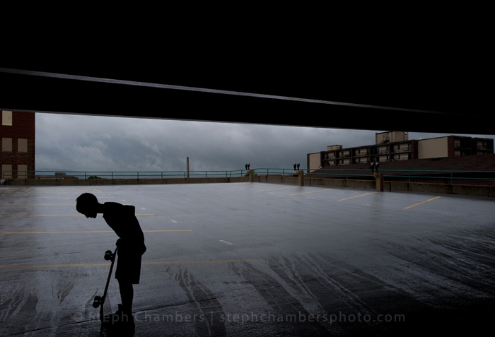 A boy waits for a storm to pass with his skateboard under the shelter of a parking garage on Thursday, July 10, 2015 in Latrobe.