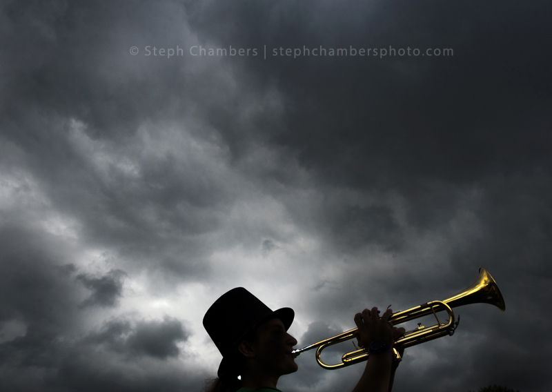 Marissa Anderton, an incoming freshman, plays her trumpet as a storm passes over Penn-Trafford's band camp at Warrior Stadium in Harrison City on Tuesday, Aug. 11, 2015. Anderton wears her top hat on Tuesdays.