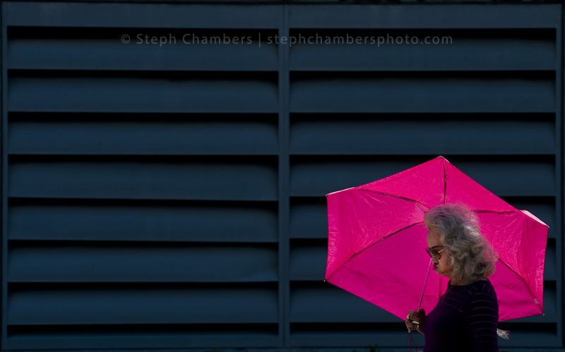 A bright umbrella shields the sun from Tuan T of Latrobe as she walks along Route 981 in Latrobe on Friday, Aug. 14, 2015.