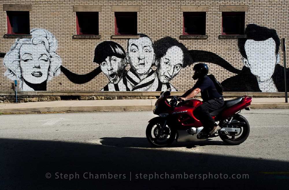 A motorcyclist cruises past a mostly complete mural on 4th Street in Jeannette on Tuesday, Sept. 15, 2015.