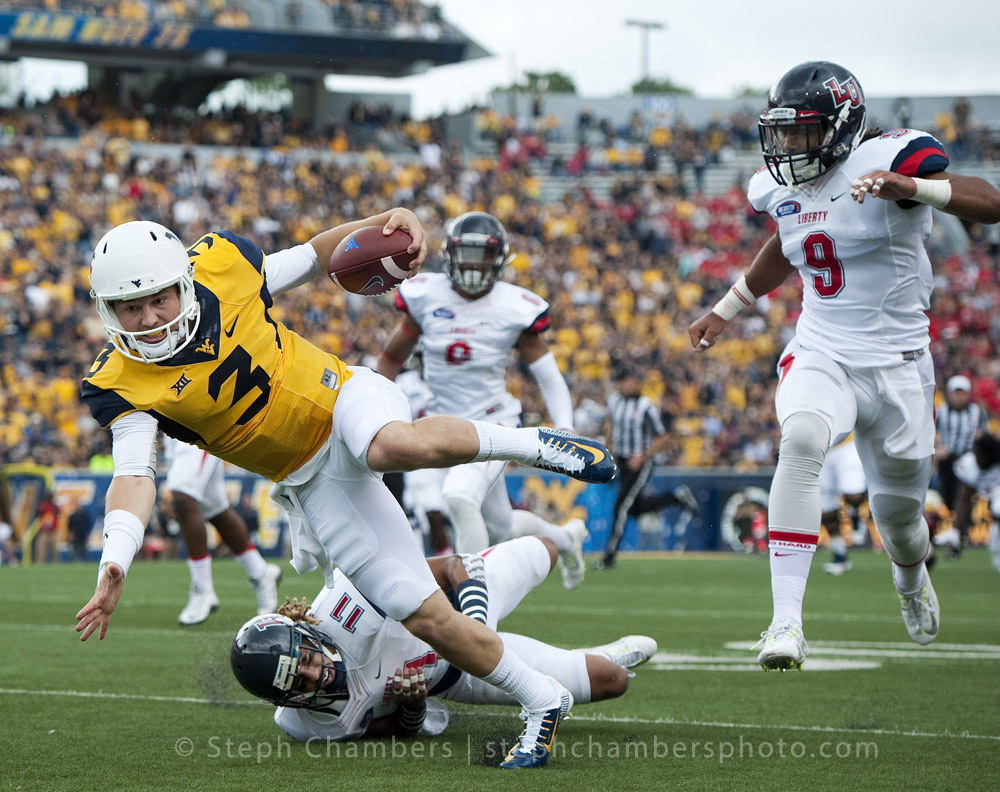 West Virginia quarterback Skyler Howard (3) gains yardage against Liberty safety Avery James (11) on Saturday, Sept. 12, 2015 at Milan Puskar Stadium in Morgantown, W.Va. WVU won 41-17.