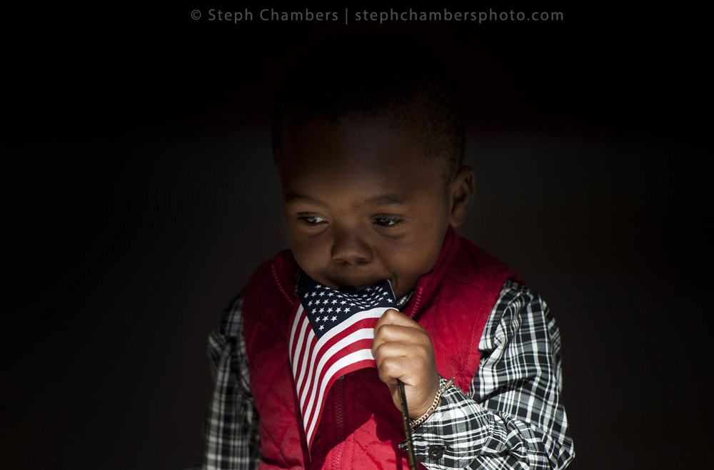 Eryn Doerue, 2, of Liberia uses a flag as a pacifier after a naturalization ceremony on Friday, Oct. 23, 2015 at Indiana University of Pennsylvania's Kovalchick Convention Center-Toretti Auditorium. The ceremony granted citizenship for 101 candidates from 44 countries, who live in the greater Pittsburgh area.