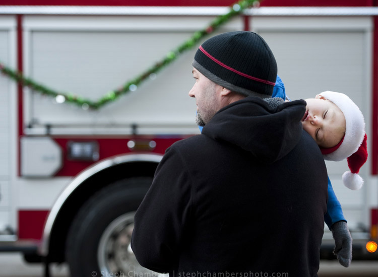 Brady Williams, 3, falls asleep on the shoulder of his father Dan, of Greensburg just before Santa's arrival during the 24th annual holiday parade on Saturday, Nov. 21, 2015, in Greensburg.