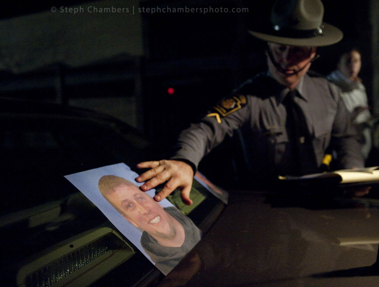 Trooper Stephen Limani lays photo of suspect Ray Shetler Jr., 31 of New Florence, on his police car during a search on Saturday, Nov. 28, 2015 in New Florence.