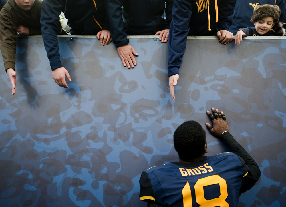 A young fan looks to congratulate West Virginia linebacker Marvin Gross (18) after West Virginia beat Texas Tech on Saturday, Nov. 7, 2015, at Milan Puskar Stadium in Morgantown, W.Va. WVU won 31-26.