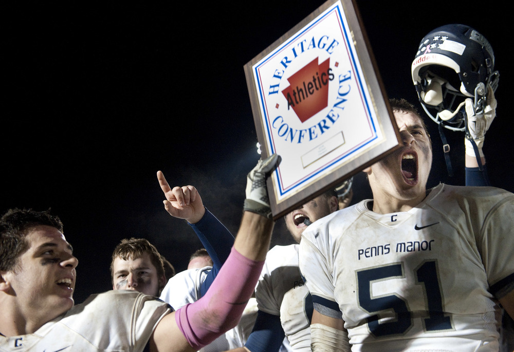 Penns Manor's Bailey Mumau hoists the Heritage Conference plaque as Zach Hnatko reacts after beating Ligonier Valley during a football game on Friday, Oct. 23, 2015 in Ligonier. Penns Manor won 19-12.