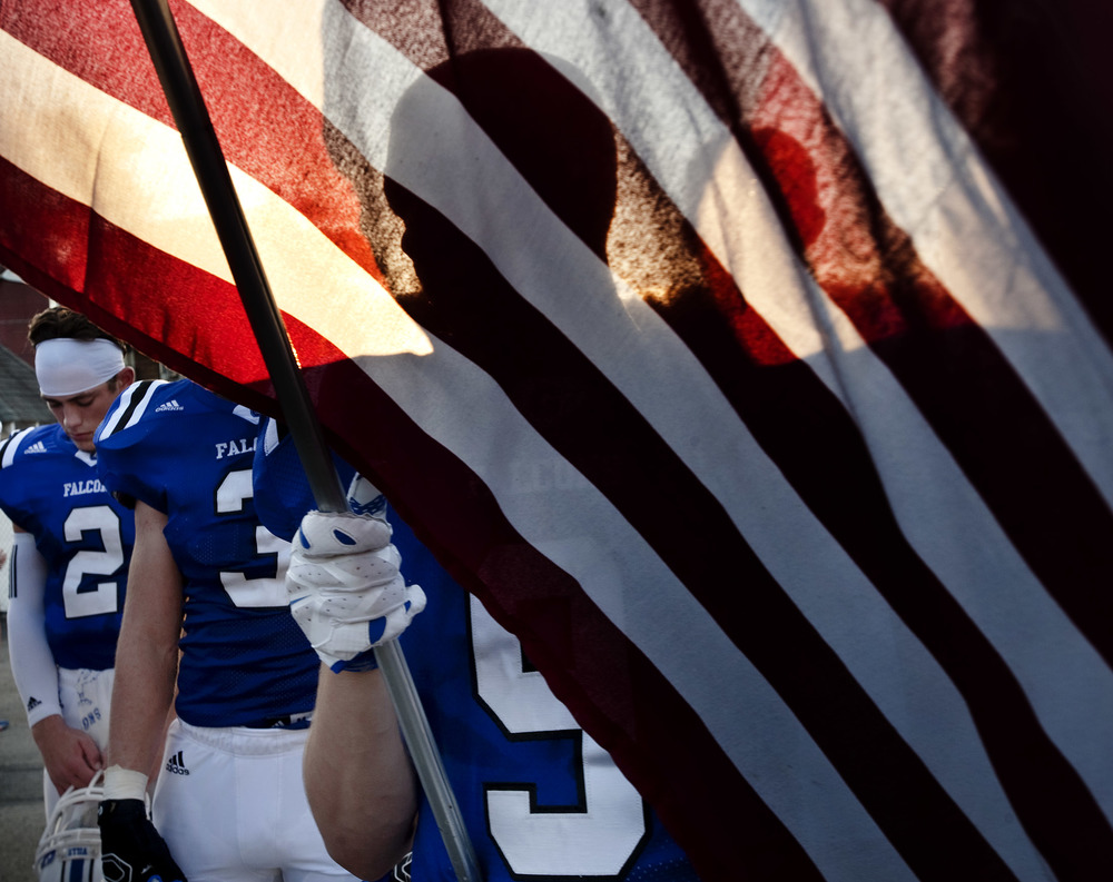 Connellsville's Tim Bish holds an American flag while listening to the national anthem prior to playing Penn-Trafford during the second week of WPIAL football on Friday, Sept. 11, 2015 at Falcon Stadium in Connellsville.