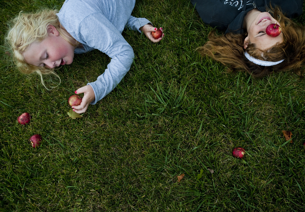Michaela Sopher reaches for the right apple in an attempt to out balance her friend Jaelyn Roupe, both 11, while the two take a break from a neighborhood apple fight along Harvey Avenue in Greensburg on Tuesday, Aug. 25, 2015.
