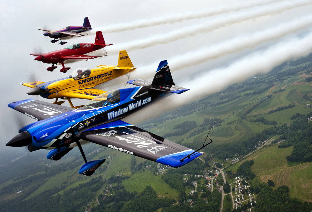 "Rob Holland in a Window World MXS, Matt Chapman in an Eagle 540, Jack Knutson in an Extra 300 S and Bill Stein in a Zivko Edge 540 collectively fly in a formation called ""The 4ce"" over rural Westmoreland County during a practice in between rain showers on Friday, June 19, 2015 in preparation for Saturday and Sunday's Westmoreland County Airshow at Arnold Palmer Regional Airport near Latrobe."