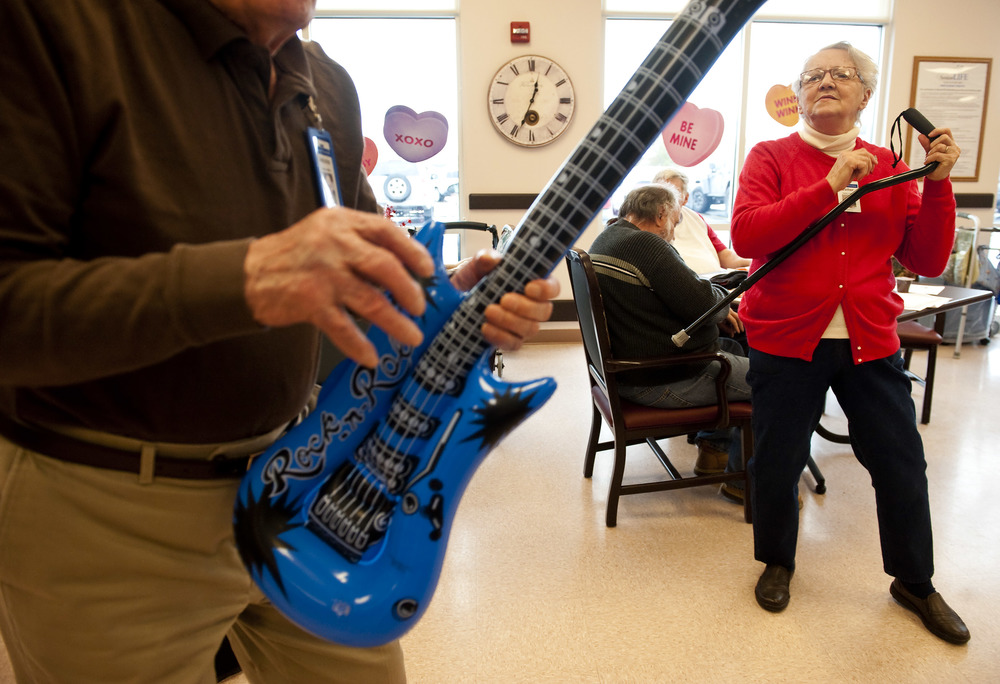 "Esther Czekaj, 75 of Mt. Pleasant, uses her cane as an ""air guitar"" during a Valentine's dance at Senior LIFE in Greensburg on Monday, Feb. 15, 2016."