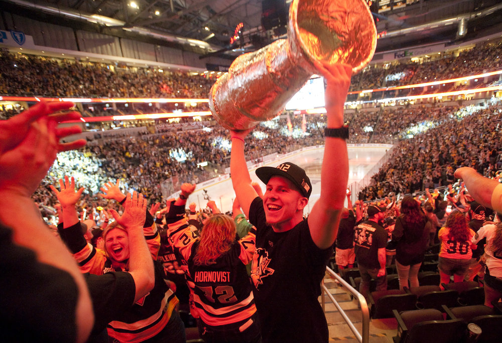 Red light from the final buzzer illuminates Mike Cummings of Overbrook as he hoists his homemade Stanley Cup during the Stanley Cup Finals, between the Pittsburgh Penguins and the San Jose Sharks, Game 6 indoor watch party at Consol Energy Center on Sunday, June 12, 2016.