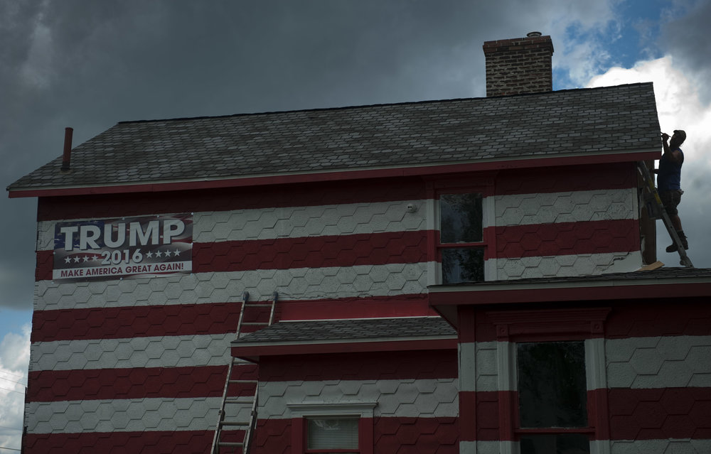 A storm cloud hovers over Dan Zak, an employee of Ligonier contractor Bob Bauer, as he finishes painting the last side of Leslie Baum Rossi's property in Youngstown on Tuesday, Aug. 16, 2016.