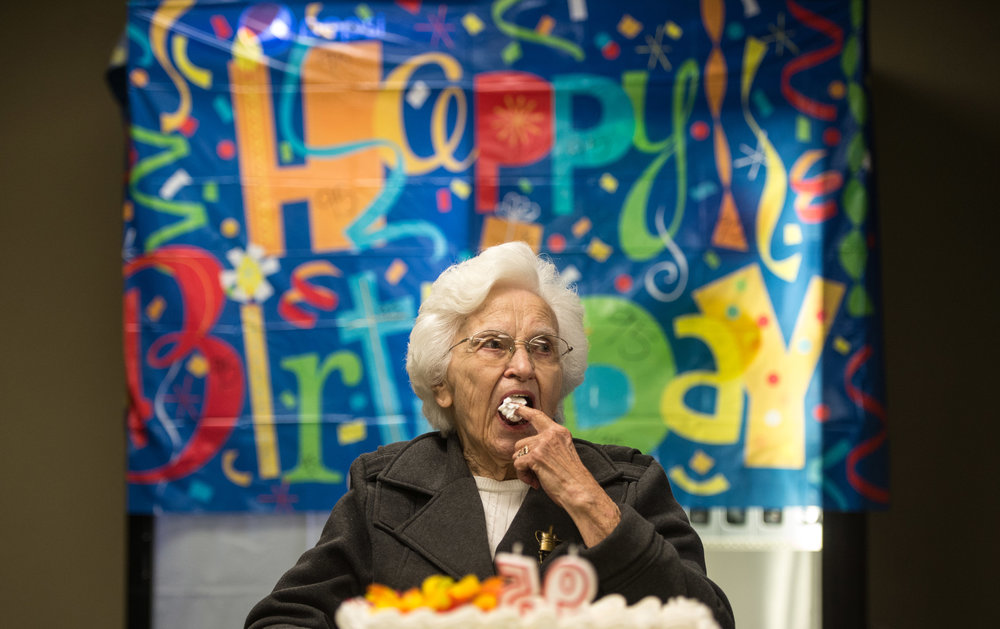 Genevieve Johnson, the longtime librarian at Seton Hill University, sneaks some icing before blowing out her candles during her 95th birthday party on Friday, Sept. 30, 2016 at Mt. Odin Golf Course in Greensburg.