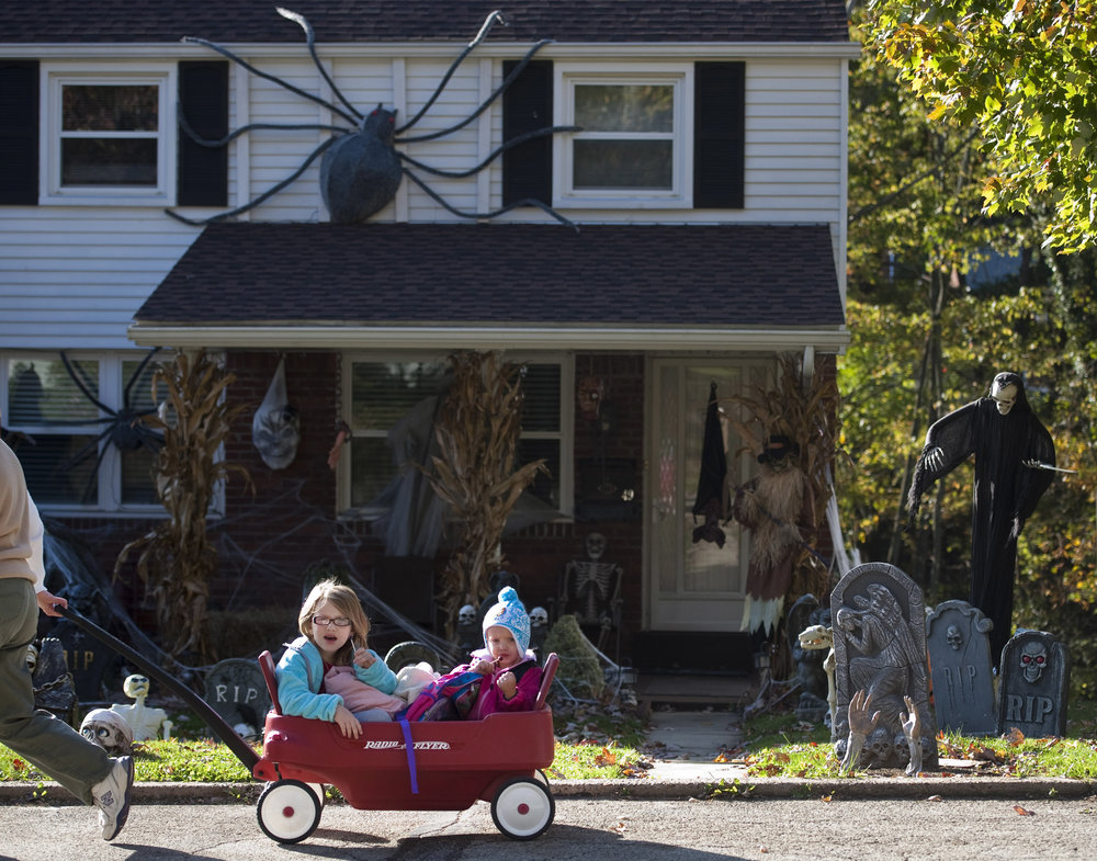 "Sisters Carissa and Abby Kelly, 5 and 2, enjoy their lollipops while admiring their neighborhood's Halloween decorations during a walk with their grandmother Linda Kelly along Forest Avenue in Greensburg on Tuesday, Oct. 25, 2016. Carissa and Abby plan to be Cruella de Vil and a dalmation puppy while trick-or-treating. ""I'm excited for lollipops and pretzels,"" Carissa exclaimed."