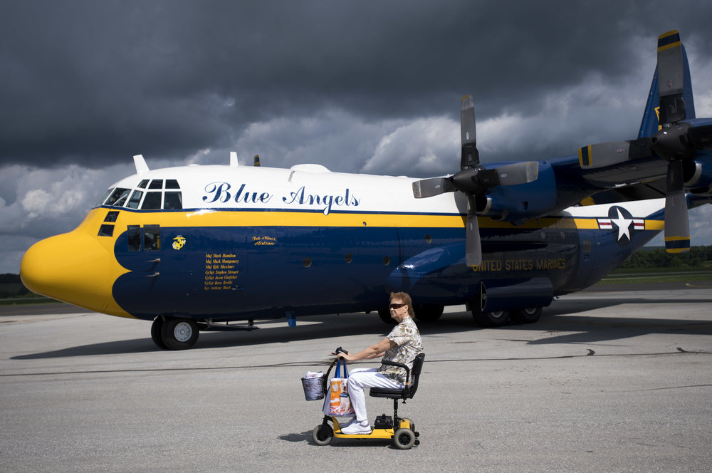 Storm clouds pass over a woman as she rides a scooter past United States Navy Blue Angels Fat Albert during the Shop 'n Save Westmoreland County Airshow on Sunday, June 25, 2017 at Arnold Palmer Regional Airport in Unity. (Steph Chambers/Post-Gazette)