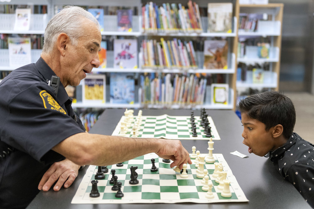 Officer David Shifren knocks off a pawn as Manoj Darjee, 9, of Carrick reacts during a weekly community chess class with Shifren on Wednesday, Sept. 12, 2018, at the Carnegie Library of Pittsburgh in Knoxville. Shifren, a Zone 4 community resource officer, leads chess classes at the Hazelwood branch every Tuesday at 5 p.m., at the Knoxville branch every Wednesday at 4 p.m. and at the South Oakland Frazier Fieldhouse near Dan Marino Field every Thursday at 5 p.m. Shifren earned his Master of Fine Arts degree in fiction writing from the University of Pittsburgh. While conducting research for one of his mystery novels, Shifren participated in a detective ride along, which sparked his interest in police work as a career. Shifren works as an officer in the evenings and writes novels and screenplays in the mornings. He also teaches a film-appreciation class at his alma mater.(Steph Chambers/Post-Gazette)