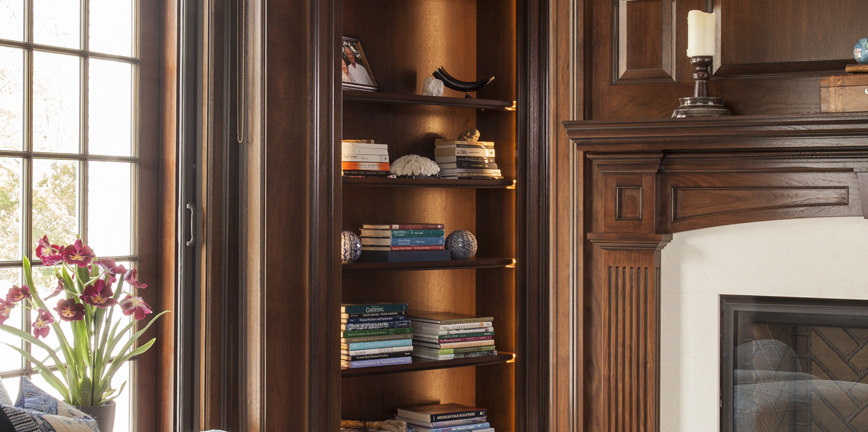 Close-up showing fireplace detail and the bookcase in the alcove beyond the sitting room.