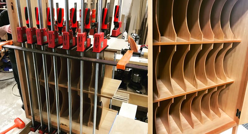 "Here you see the the music cabinet's interior vertical partitions that would help Gilda organize her sheet music. On the left you see the partitions clamped in KR+H's shop. When Paul saw this image he smiled and said, ""You can never have too many clamps! I've thought that all my life!"""