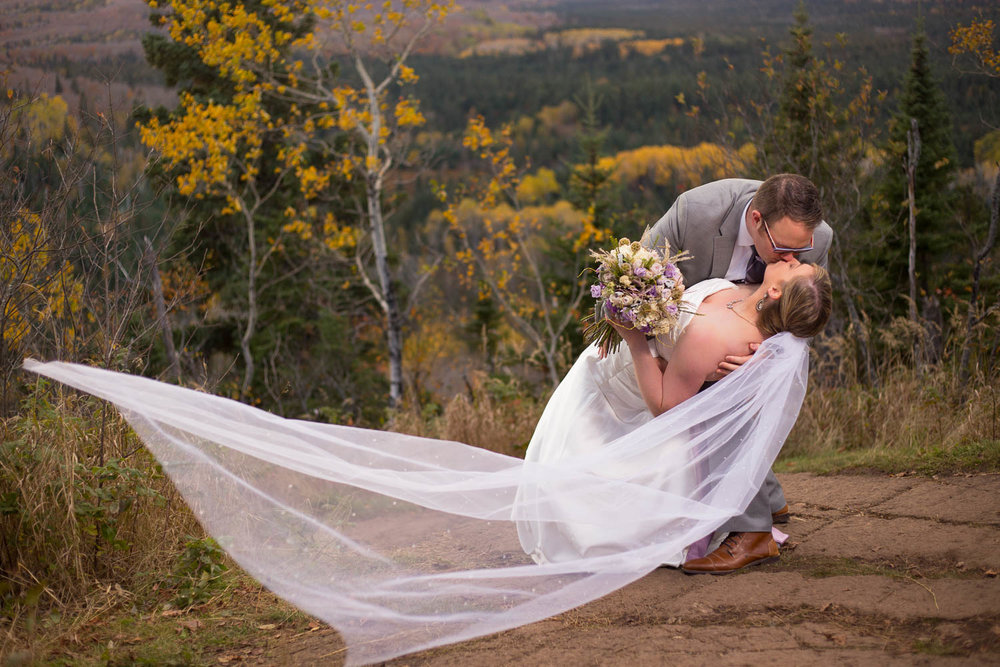 wedding bride and groom kissing on top of oberg mountain with floating veil north shore duluth minnesota