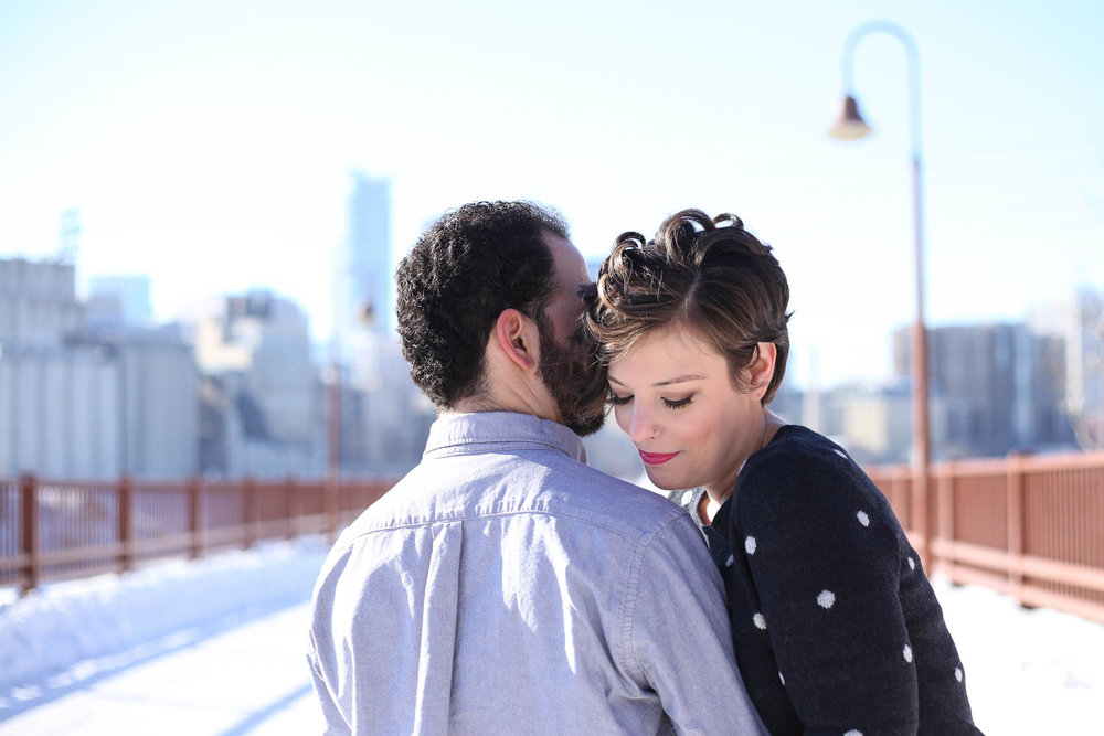 Engagement couple on stone arch bridge cuddling