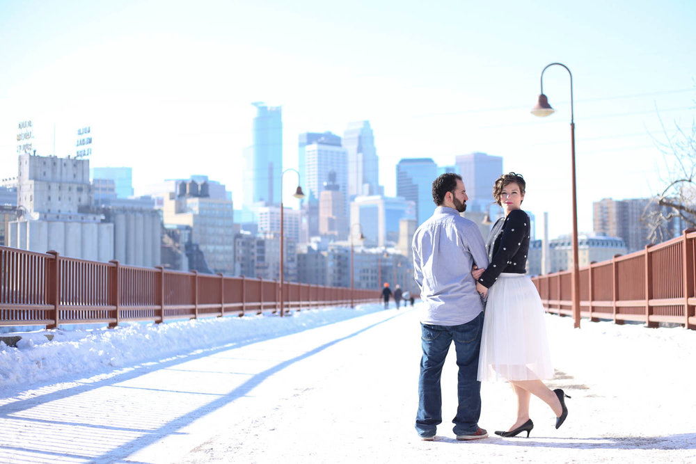 Engagement couple in front of Minneapolis skyline on the stone arch bridge