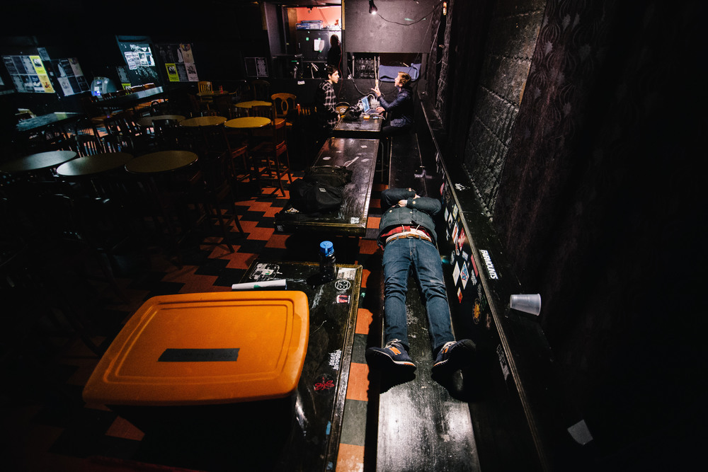 Jeff Russell lies on a bench behind the merch table shortly after loading into the Hard Luck Bar in Toronto, Ontario, Wednesday April 6, 2016. After the five hour drive we were all feeling a slight bit of exhaustion.