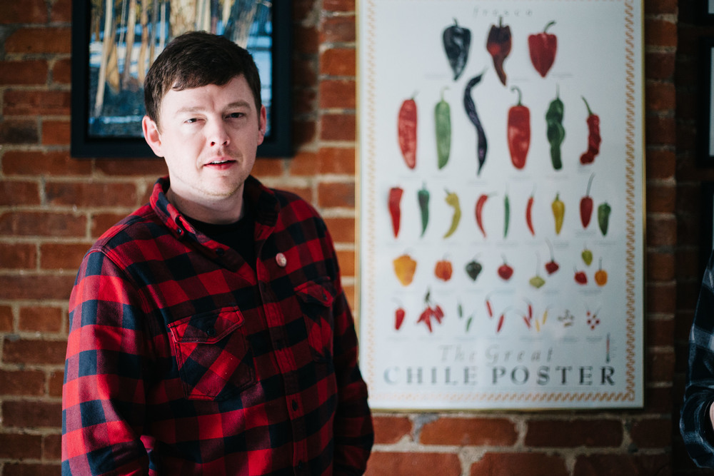 "Jeff Russell, also known as Pepper, stands in front of a chile pepper poster at the Sladkowski home in Toronto, Ontario, Thursday April 7, 2016.  The nickname Pepper began as a joke but as tour went on, everyone would occasionally be called Pepper.  Ex: "" You did a good job there, Pepper. Have this beer."""
