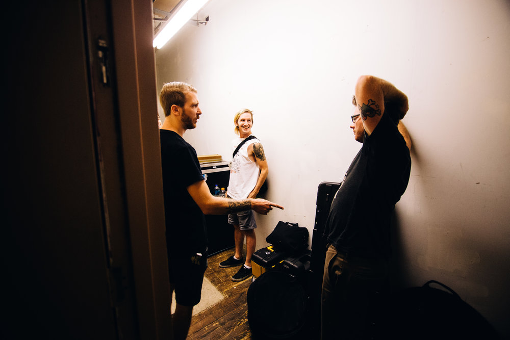 Steve (left), Josh (center) and Ryan (Right) talk in the back hallway of the venue as the band loads into Studio Luloo.