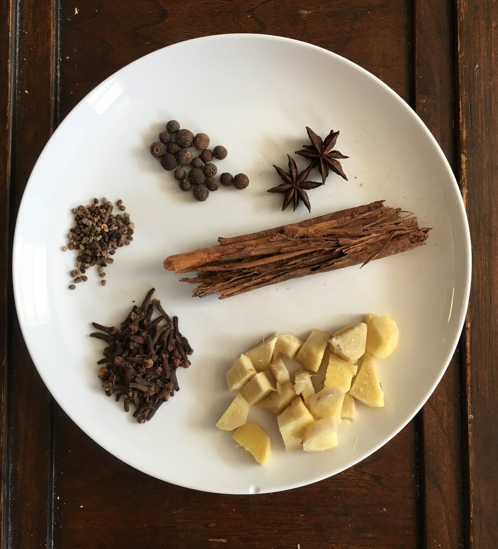 From 1 o'clock going clockwise: star anise, cinnamon sticks, fresh ginger, cloves, cardamom seeds, allspice berries.
