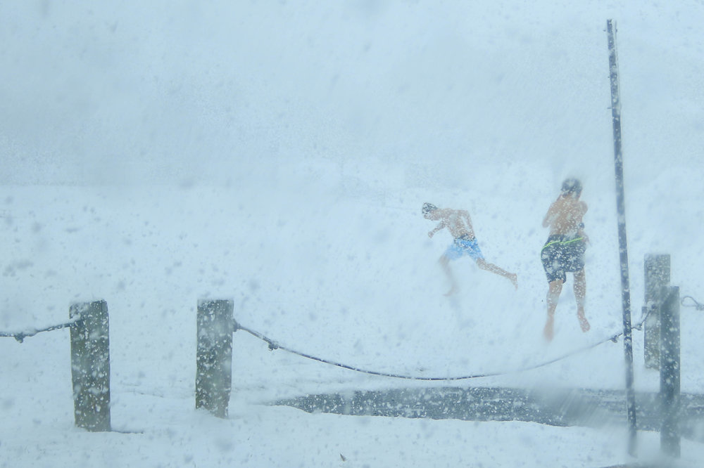 Two boys in bathing suits sprint through Fiala Fields in Camp Hill, Pa. during a snowstorm on Sunday, March 25, 2018.