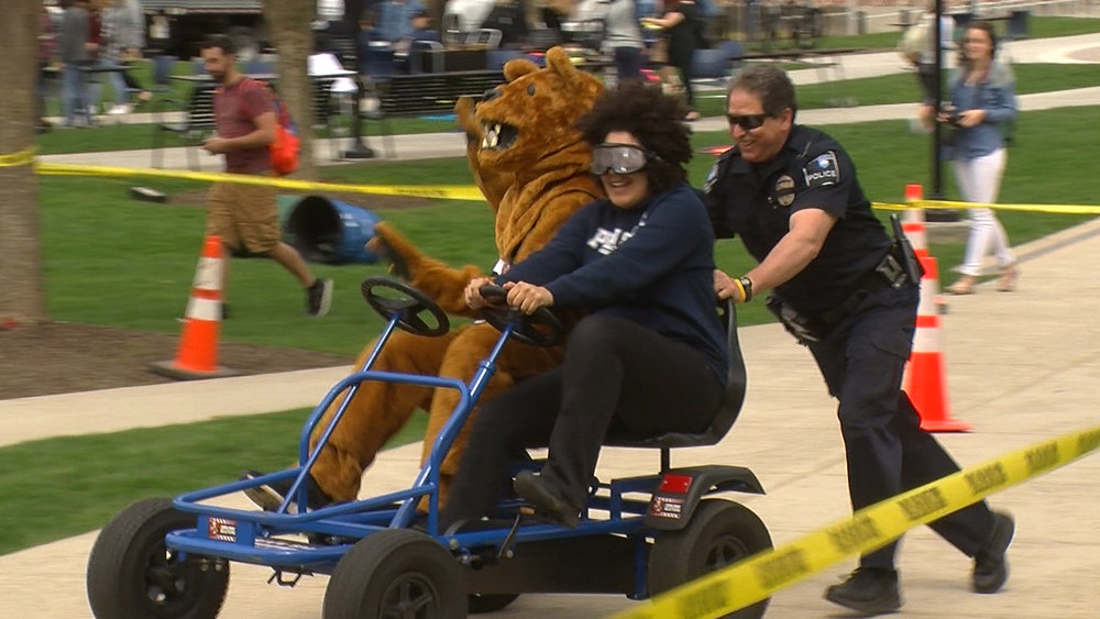 Officer Richard Rocco pushes a cart with a student and the Nittany Lion on it during an exhibit focusing on the dangers of driving under the influence at Penn State Harrisburg's Wellness Day on Tuesday, April 24, 2018.