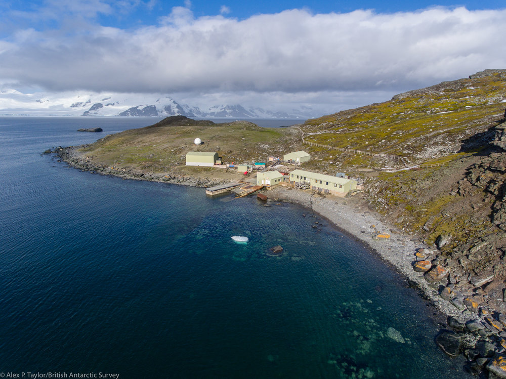 An aerial view of Factory Cove and Signy research Station on Signy Island, Antarctica. Coronation Island can be seen in the distance, across Borge Bay. A British science presence has been doing research on the island since the mid 1940's. Whalers used the site decades before that. The prominent fence running across the base of the slope keeps the nearly extinct, but now booming, fur seal population from destroying the delicate moss banks beyond.