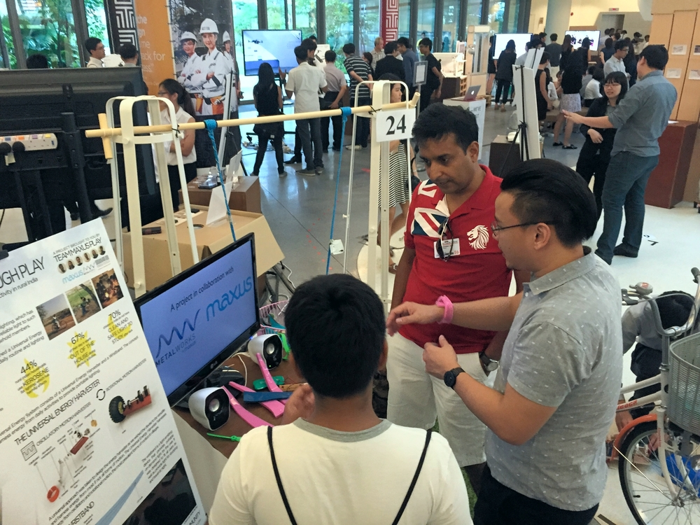 Ken from the capstone project group explains how the flexible silicon wristband works to curious onlookers.
