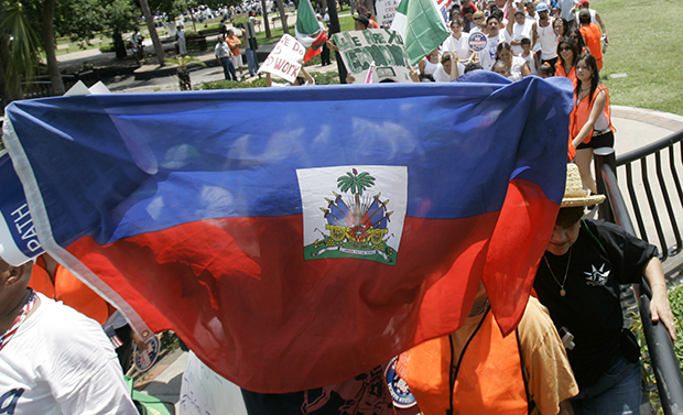 A protester holds up a Haitian flag during a march for immigration reform in Orlando, Florida.