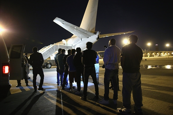 Undocumented immigrants wait to be loaded onto an Immigration and Customs Enforcement (ICE), charter jet early on October 15, 2015 in Mesa, Arizona. The immigrants were to be flown to other states for follow-on ICE deportation flights to the Caribbean, Mexico and Central America. ICE builds deportation cases against thousands of undocumented immigrants, many of whom, they say, have criminal records. The number of ICE detentions and deportations has dropped in the last two years since some states adopted laws limiting how state law enforcement agencies cooperate with federal immigration authorities. (Photo : John Moore/Getty Images)