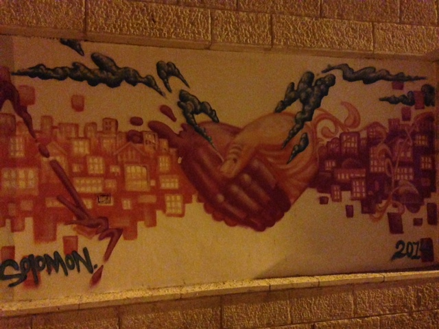 Street art depicting hands grasping in Jerusalem