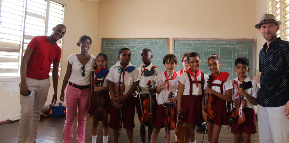 LUCIEN JAMEY OF THE OPEN STRING WITH 2ND and 3RD GRADE STUDENTS AND TEACHERS AT THE ESCUELA ELEMENTAL DE ARTE PAULINA CONCEPCIÓN IN HAVANA, CUBA. THIS MUSIC-FOCUSED PUBLIC SCHOOL TRAINS STUDENTS AGES 7 THROUGH 14 FOR MUSICAL CAREERS. THE OPEN STRING DONATED OVER 300 STRINGS FOR VIOLINS, VIOLAS, AND CELLOS TO ADDRESS THE LACK OF FUNDS AND ACCESS TO STRINGS AND SUPPLIES IN THE NATION.
