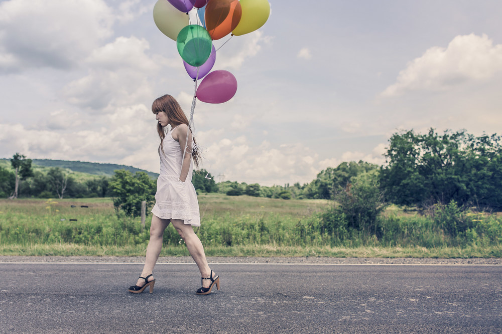 Girl on road with balloons