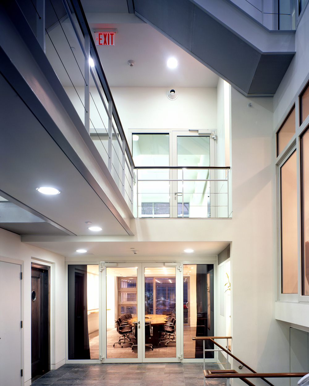 "These two abutting townhouses were renovated to create business offices and an apartment. By removing a portion of the central bay of one of the buildings, a skylit ""expanded stair enclosure"" was created.  The circulation in this central space is an exhilarating experience and the space serves as a forum for informal interaction between staff members of different companies. The front façade was restored, new wood windows were made to match the existing windows, the mansard and the sunroom were rebuilt and a new roof was installed. Both buildings had their original Otis elevators restored.  In the duplex residence that straddles the top of both buildings, a portion of the fifth floor in one building was removed to create a double height living room.  The backdrop to this soaring living space is a double-height, American walnut cabinet featuring a display of the owner's African mask collection. An open walnut stair leads up to the rebuilt sunroom and the bridge to the bedrooms."