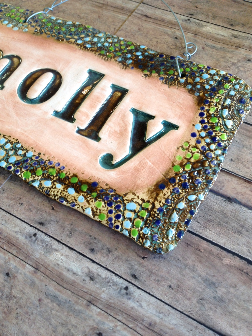Our Molly sign is shown here in our natural earth tone color scheme and highlighted with lime green, cobalt blue and light blue.