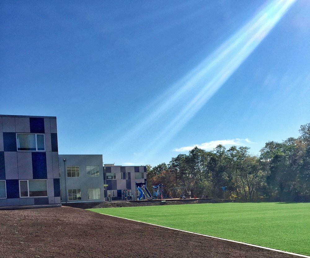 Looking across the turf field towards one of the academic buildings and the playground.
