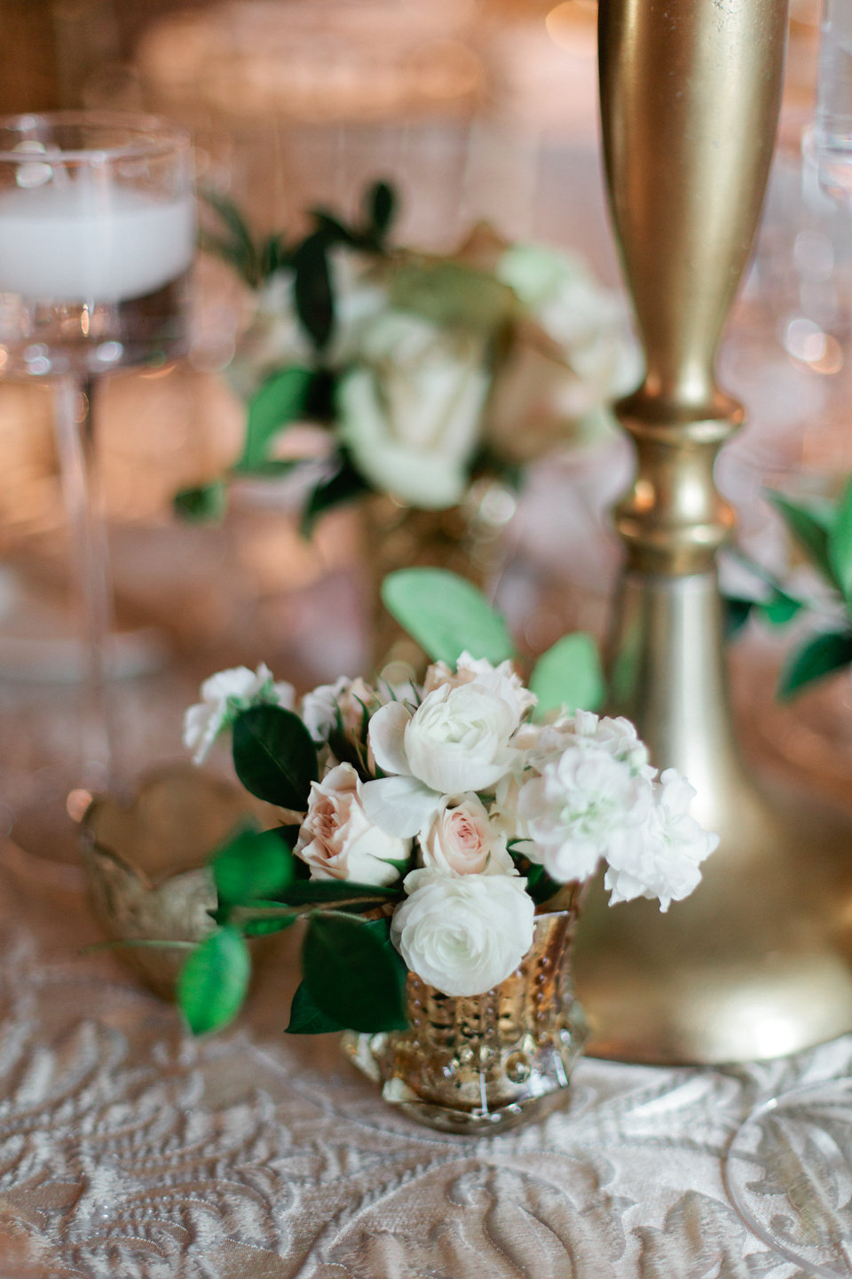 Blush spray roses with ivory ranunculus buds at luxury wedding reception